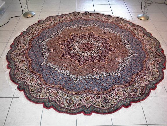 Round Persian rug. Example or what round Persian rugs look like. Handmade Persian rugs like this are typically made of fine wool and large silk highlights.